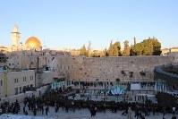 エルサレム旧市街にある「嘆きの壁」(正面)。ユダヤ教の聖地で、例年1000万人が訪れる。黄金に輝く「岩のドーム」(左上)のある一角はイスラム教徒の聖域だ=エルサレム旧市街中心部で2016年1月6日、大治朋子撮影