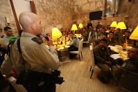 軍が準備した食事会で、司令官(写真左手前)の言葉に耳を傾ける「ローン・ソルジャー」(単身兵士)たち=エルサレム旧市街中心部で2016年1月6日、大治朋子撮影