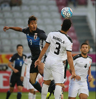 Musashi Suzuki, left, jumps for a header during the first half of the Asian Under-23 Championship semifinal between Japan and Iraq in Doha, Qatar, on Jan. 26, 2016. (Mainichi)