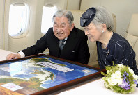 Emperor Akihito and Empress Michiko look at a map on their flight to the Philippines on a Japanese government aircraft on Jan. 26, 2016. (Pool photo)