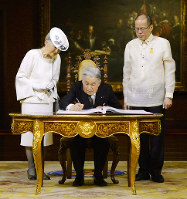 The Emperor signs a guest book at Malacanang Palace, the official residence of Philippine President Benigno Aquino (right) on Jan. 27, 2016. (Pool photo)