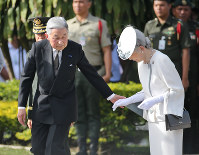 Emperor Akihito takes Empress Michiko's hand as they head to the Tomb of the Unknown Soldier at Heroes' Cemetery in Manila on Jan. 27, 2016. (Pool photo)