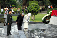 The Emperor and Empress bow after laying a wreath of flowers at the Tomb of the Unknown Soldier in Manila on Jan. 27, 2016. (Pool photo)