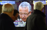 甘利明・経済再生担当相辞任の記者会見を映し出す街頭テレビ=東京都千代田区で2016年1月28日午後7時5分、宮間俊樹撮影
