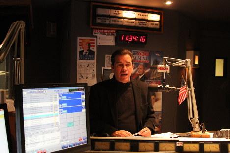 ワシントンのWMALラジオのスタジオでトーク・ラジオ番組を担当するクリス・プラントさん。壁には「リベラル・メディアは信じない」というステッカーが張られていた=22日、和田浩明撮影