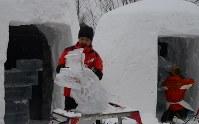 氷彫刻の制作に取り組む参加者たち=日光市の湯ノ湖湖畔で