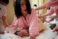 助産師に手を添えられながら女の子の赤ちゃんを産み、ほっとしたような表情を見せる母の藤井恵さん=2011年4月11日午後0時5分、森田剛史撮影