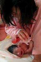 生まれたばかりの稟ちゃんの手に触れる母の藤井恵さん=2011年4月11日午後0時4分、森田剛史撮影