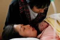 生まれたばかりの稟ちゃんを抱く母の藤井恵さんと愛娘の顔を見つめる父順治さん(上)。皆、ほっとしたような表情を見せた=2011年4月11日午後0時29分、森田剛史撮影