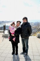 被災した街を見下ろす日和山で、父順治さんは稟ちゃんに震災前の写真を見せ、「元はこんな街だったんだよ」と語りかけ、母恵さんは「この子が大きくなった時、街は復興しているのかな」とつぶやいた=2013年2月21日、森田剛史撮影