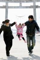 被災した街を見下ろす日和山で、手をつないだ父順治さんと母恵さんに持ち上げられ、笑顔を見せる藤井稟ちゃん=2013年2月21日、森田剛史撮影