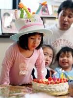 4歳の誕生日にケーキのろうそくを吹き消す藤井稟ちゃん(左)。右奥は父順治さん=宮城県石巻市で2015年4月11日、森田剛史撮影