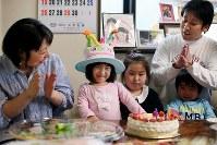 4歳の誕生日にケーキの前で笑顔を見せる藤井稟ちゃん(左から2人目)と、お祝いする父順治さん(右奥)と母恵さん(左端)=2015年4月11日、森田剛史撮影