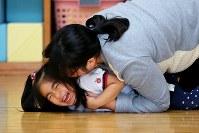 親子体操教室で母恵さんと触れ合い、笑顔を見せる藤井稟ちゃん(下)=2015年12月16日、森田剛史撮影