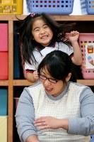 親子体操教室で笑顔を見せながら母恵さんの肩をたたく藤井稟ちゃん(奥)=2015年12月16日、森田剛史撮影