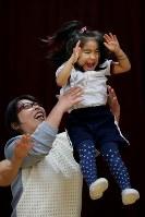 親子体操教室で母恵さんに持ち上げられ、喜ぶ藤井稟ちゃん(右)=2015年12月16日、森田剛史撮影