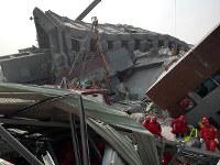地震で崩壊したマンションで救出作業にあたる警察、消防の隊員たち=台湾南部の台南市で2016年2月6日、鈴木玲子撮影