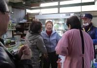 「井上青果店」営業最後の昨年12月30日、古くからの友人が訪れ、感極まる井上京子さん(中央)と傍らに立つ夫の準一さん(右)=東京都新宿区で内藤絵美撮影