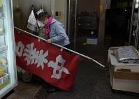 「井上青果店」営業最後の日、のぼりを取り込む井上京子さん=2015年12月30日午後6時16分、内藤絵美撮影