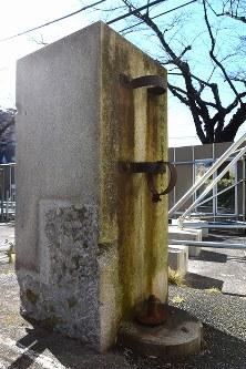 京成電鉄「旧寛永寺坂駅」の元駅舎のそばに残る碑。表面には「國威宣揚」、側面には神武天皇即位紀元2600年を記念したものだと記され、後方には国旗を掲揚できるようになっていた=東京都台東区上野桜木で2016年2月2日午前11時3分、竹内紀臣撮影