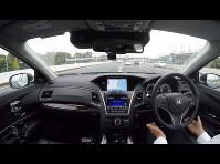 首都高速道路で走行したホンダの自動運転実験車、車線変更の際もハンドルから手を離している=2015年10月、本田技研工業提供