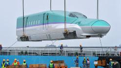 輸送船からクレーンで陸揚げされる北海道新幹線の先頭車両=函館港で2014年10月、手塚耕一郎撮影