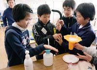 弁理士による授業の後、片手でシャンプーが出るように工夫されたボトルなどに触れる児童たち=徳島県神山町阿野の広野小学校で、数野智史撮影
