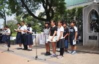 昨年の式典に参加、平和祈念碑の前で非核平和都市宣言を読み上げる子供。碑の向こうは壁に遮られている
