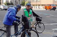 自転車レーンについての説明を聞く自転車運転者(左)=大阪市中央区の本町3丁目交差点で、千脇康平撮影