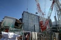 原発事故の爪痕が残る3号機の原子炉建屋と大型クレーンでつり上げられるがれきの吸引装置=福島第1原発で2016年2月12日午後0時24分、森田剛史撮影