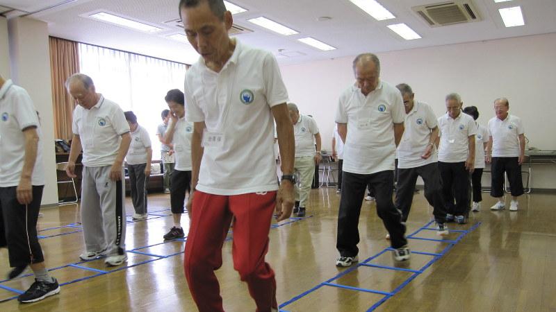 声を出して数を数えるのと同時に、マス目を使ってステップを踏みながら進む参加者=愛知県大府市で細川貴代撮影
