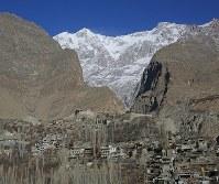 カラコルム山脈に囲まれたカリマバードの村。村の北側、奥右にウルタル2峰(7388メートル)、奥左にウルタル1峰(7329メートル)がそびえ立つ。山の斜面にへばりつくように家々が建ち並ぶ=パキスタン・カリマバードで2015年12月12日、長谷川直亮撮影