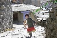 石畳の坂をヤギを連れて歩く女の子=パキスタン・カリマバードで2015年12月11日、長谷川直亮撮影