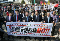 From left, Japan Innovation Party lawmaker Akihiro Hatsushika, People's Life Party member Takeshi Hidaka, Japanese Communist Party vice chairman Akira Koike, former Prime Minister Naoto Kan of the Democratic Party of Japan, and Social Democratic Party lawmaker Seiji Mataichi hold a banner together at an anti-Abe government march, on Feb. 14, 2016. (Mainichi)