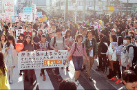 Protesters march through a crowded street in the Harajuku area in Tokyo's Shibuya Ward, on Feb. 14, 2016. (Mainichi)