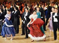 えんび服姿の元タカラジェンヌと踊る水津記者(中央の赤いドレス)=兵庫県宝塚市で、森園道子撮影