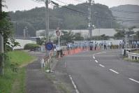 川内原発正門(中央)前を通る県道43号。昨年8月の1号機再稼働の直前、正門前で反対集会が予定されたため警察官らが警備に当たっていた