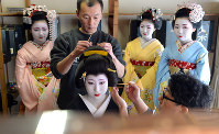 A geisha has her hairdo fixed in preparation for the forthcoming