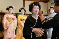 A geisha has her makeup applied during preparations for the forthcoming