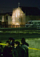 Police officers and the news media are seen late on Feb. 18, 2016 near a church where a man took a female counselor hostage, in Sakura, Chiba Prefecture. (Mainichi)