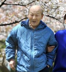 介護職員とともに桜並木の下を散歩する「太郎さん」=大阪市内で2014年4月、梅田麻衣子撮影
