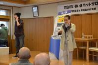 犯人役の男性(左)から電話で指示を受けながらATMを操作し、お金を振り込んでしまう被害者役の女性=韮崎市穴山町で