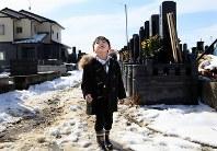 祖父母と叔父の1周忌の法要でやっと完成した墓に訪れた佑星君(6)。手を合わせた後、空を見上げた足元には、花束を手向けた時と同じ長くつがあった=宮城県石巻市で2012年2月26日、梅村直承撮影