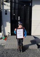 斎藤佑星君(7)。宮城県石巻市の借り上げ仮設住宅でそろばん教室の賞状を手に。「1年生で友達がたくさんできたけど100人はいないよ。算数が大好きだよ」=2013年2月17日、梅村直承撮影