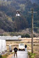 小型無人機「ドローン」による貨物輸送実験で機体を飛ばす関係者(左)=徳島県那賀町和食郷で2016年2月24日午前11時4分、数野智史撮影