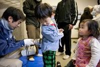飯舘村役場では子どもたちのスクリーニングと甲状腺の内部被ばく検査が行われた。放射線被ばく検査から3カ月以上が過ぎた7月、福島県では原発周辺の子ども約1080人のうち45%が甲状腺に被ばくしていたことが明らかになった=2011年3月30日、福島県飯舘村(写真家・野田雅也)