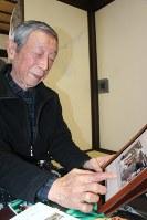 いとおしそうに一枚一枚写真をめくる渡辺昭夫さん。「毎回海外旅行をしたような気分になる」という=横浜市戸塚区の自宅で