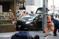 A passenger car is seen wrecked on a sidewalk after a collision with pedestrians near Osaka Station in Osaka's Kita Ward on Feb. 25, 2016. (Mainichi, photo partially modified)
