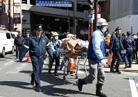 An emergency rescue team is seen carrying an injured person on a stretcher near Osaka Station in Osaka's Kita Ward on Feb. 25, 2016. (Mainichi)