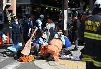 Emergency rescue workers give first aid to an injured person involved in the accident near Osaka Station in Osaka's Kita Ward on Feb. 25, 2016. (Mainichi)